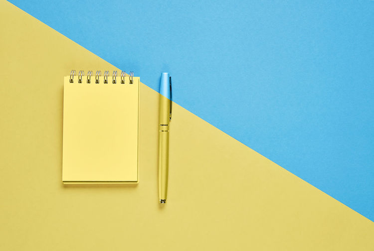 Close-up of notepad and pen on colored background