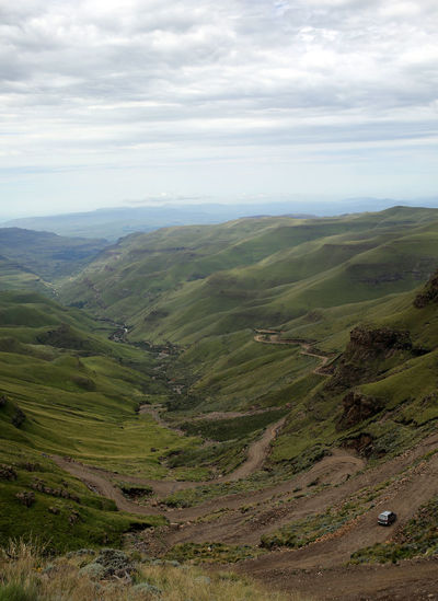 """""""Sani Pass v"""" Landscape Scenics - Nature Sky Environment Tranquil Scene Cloud - Sky Tranquility Beauty In Nature Non-urban Scene Green Color Mountain Nature Day No People Plant Land Idyllic Outdoors Grass Rolling Landscape Trail Sani Pass South Africa Lesotho KwaZulu-Natal"""
