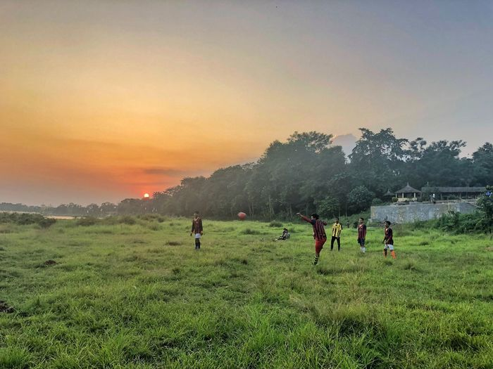 Boys playing soccer on grassy field against sky during sunset