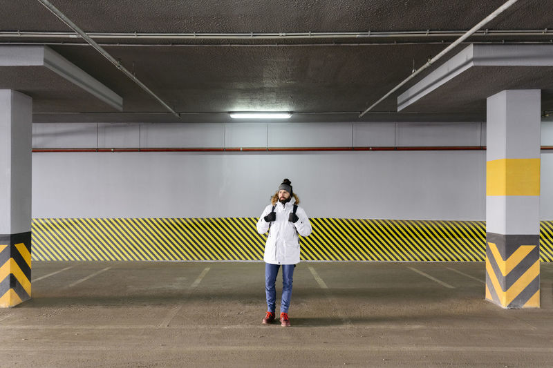 Full length of woman standing against illuminated wall