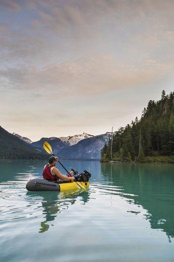 People rowing boat in lake against sky