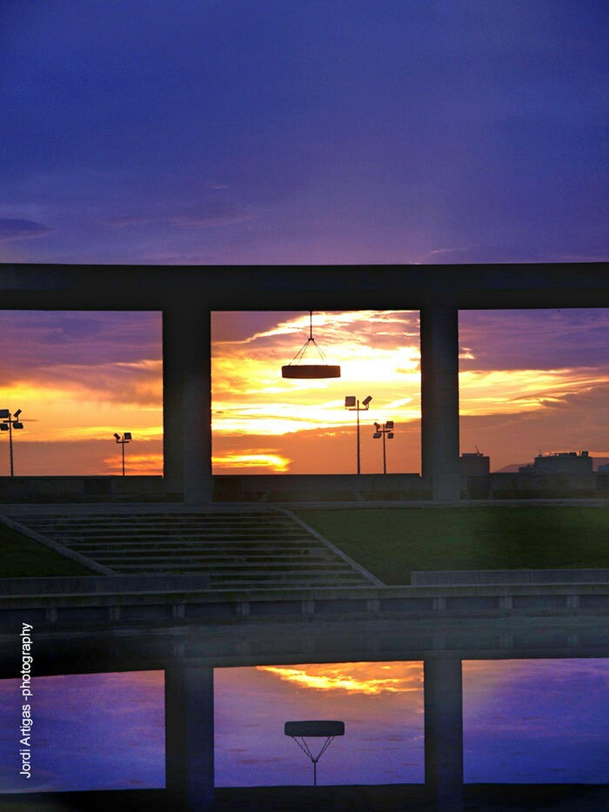 sunset, sky, built structure, architecture, cloud - sky, orange color, cloud, yellow, blue, low angle view, transportation, silhouette, outdoors, dusk, illuminated, no people, railing, building exterior, bridge - man made structure, sunlight