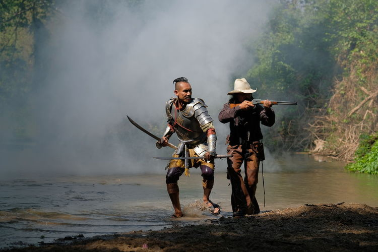 Warriors with weapons in forest