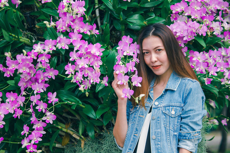 Portrait of beautiful young woman standing by pink flowering plants