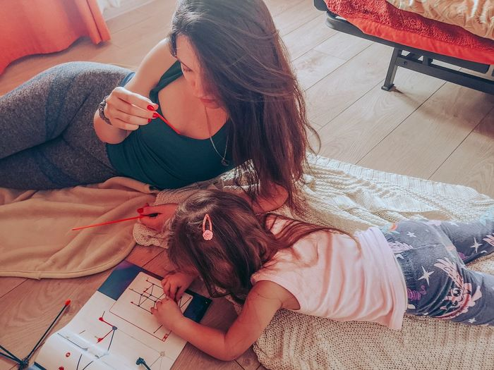 High angle view of mother with daughter making model at home