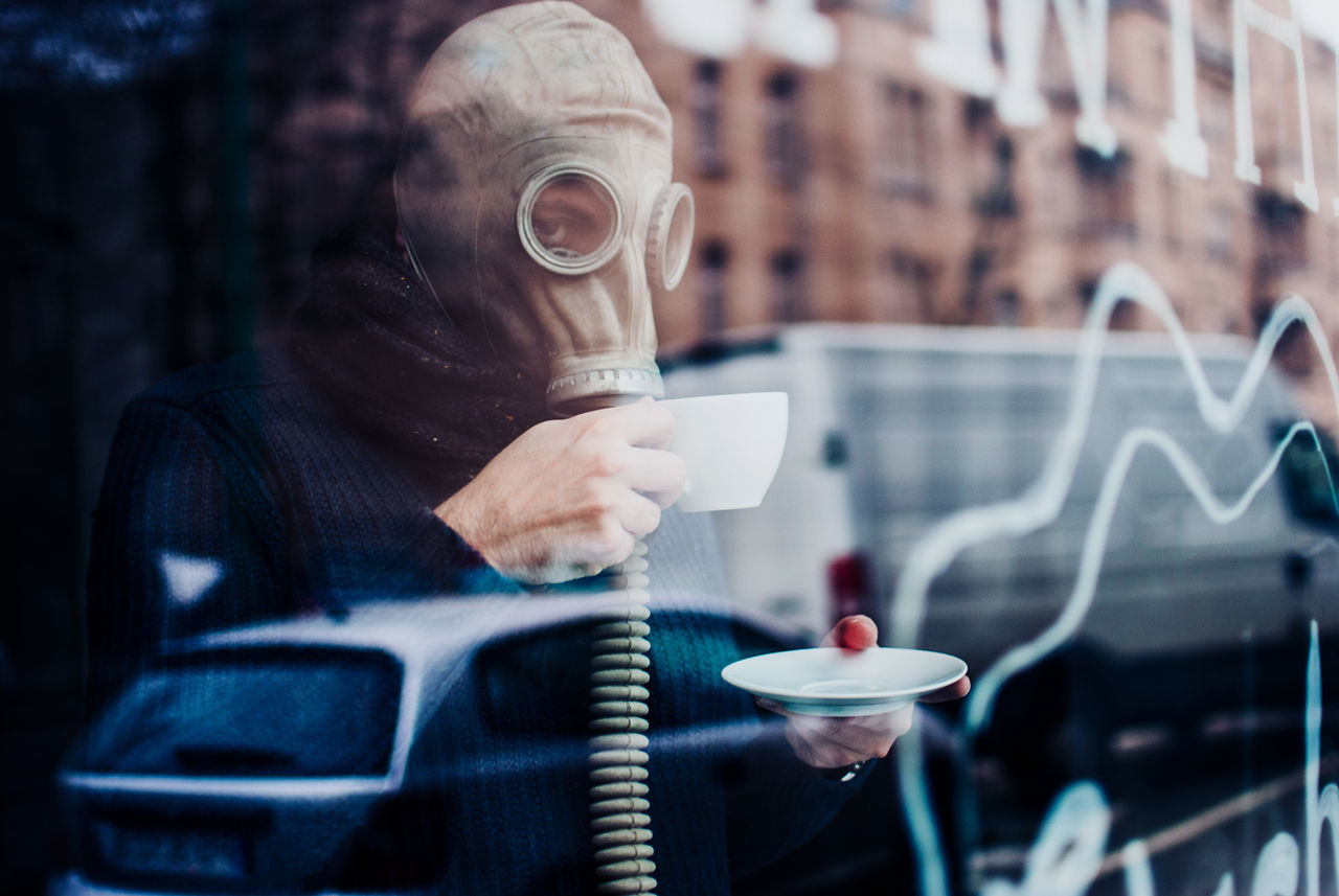 Man in gas mask holding coffee cup in city