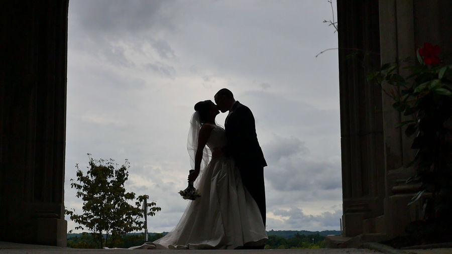 BRIDE AND GROOM KISSING AGAINST CLOUDY SKY