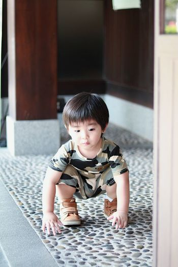 Full length of cute baby boy crouching on porch