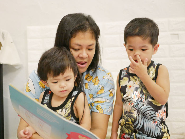 Mother reading book with daughters at home