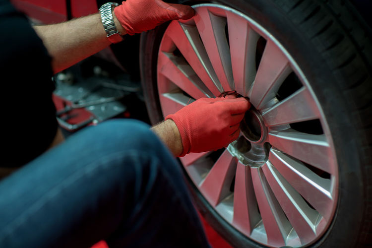 Mechanician changing car wheel in auto repair shop Adult Auto Repair Shop Car Day Hand Holding Human Hand Land Vehicle Mechanic Mode Of Transportation Motor Vehicle Occupation One Person Real People Repairing Shopping Spoke Tire Transportation Wheel Working