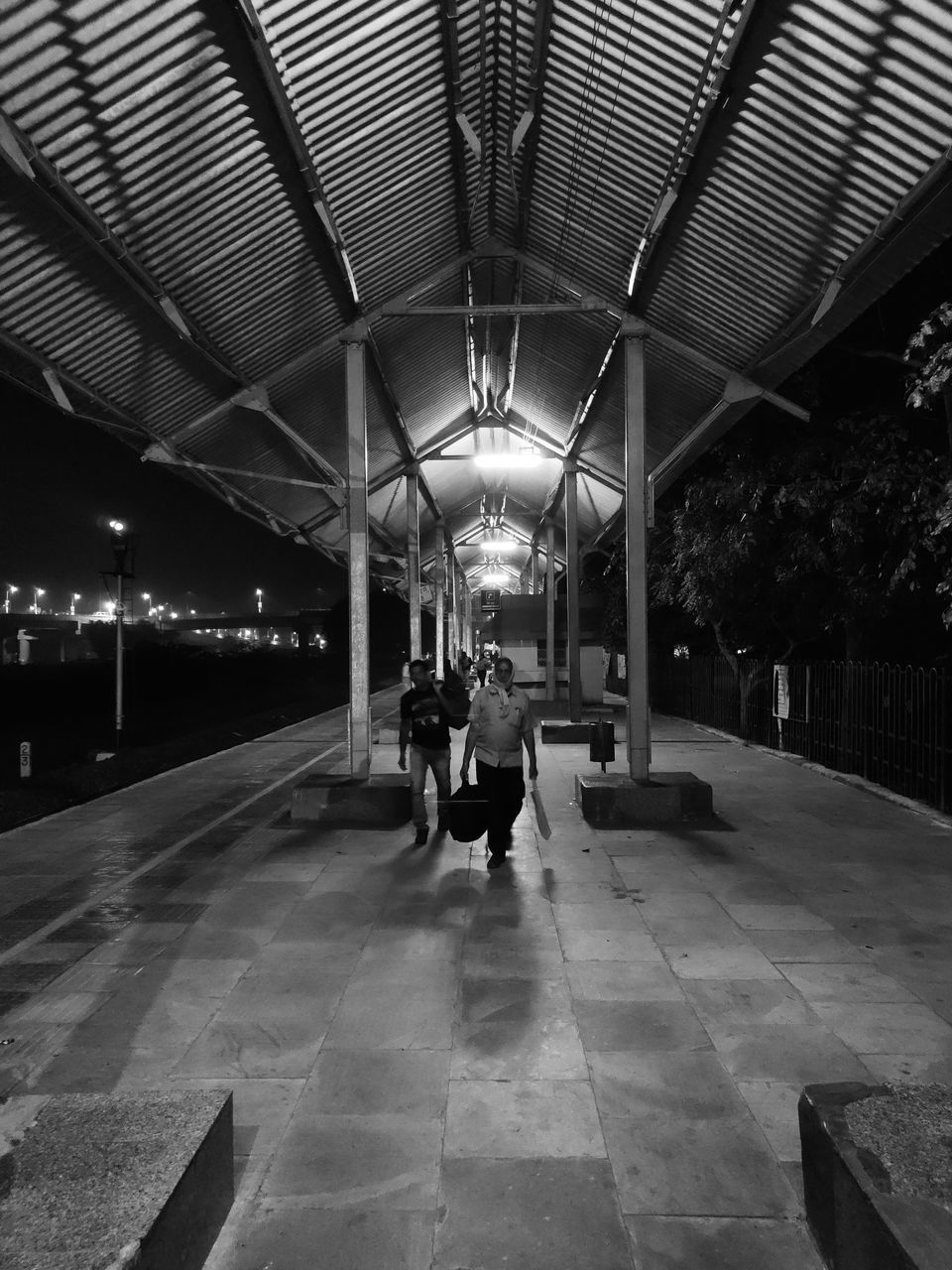 REAR VIEW OF MAN AND WOMAN WALKING IN ILLUMINATED UNDERGROUND