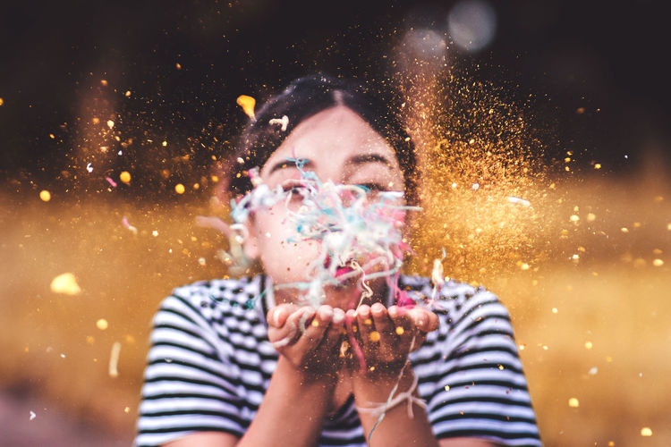 "add a little confetti to each day. ""Close-Up Of Smiling Young Woman Blowing Confetti While Standing Outdoors"" Adult Adults Only Blowing Bubble Wand Cheerful Close-up Confetti Focus On Foreground Front View Glitter Happiness Headshot Holding Night One Man Only One Person Only Men Outdoors People Portrait Real People Smiling Sparkler Young Adult Be. Ready."