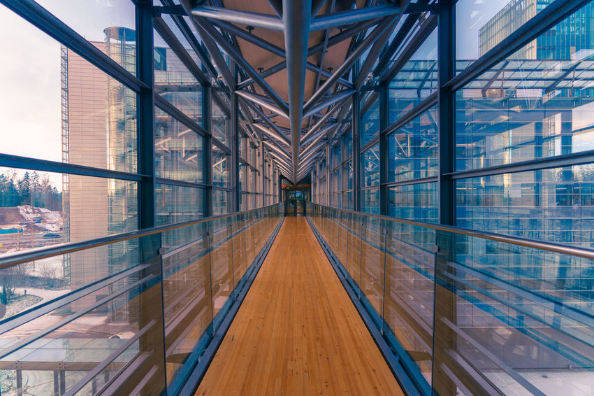 Glassed walkway in a modern office building Architecture Lines Metallic Structure Perspective Architecture Bridge - Man Made Structure Built Structure Connection Converging Lines Day Glass Indoors  Metal Metallic Metallic Construction Modern No People Reflection Walkway Wooden Floor The Architect - 2018 EyeEm Awards