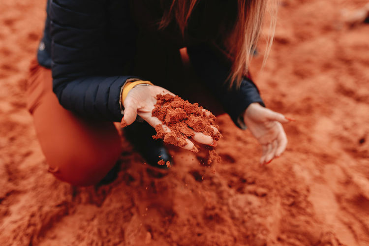 Midsection of woman holding sand