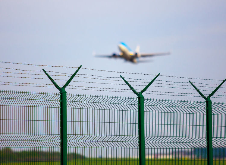 Airport fence with airplane Aeroplane Air Aircraft Airplane Airport Airport Fence Area Business Departure Fence Jet No People Out Of Focus Outdoors Over Plane Security Sky Take Off Travel Traveling