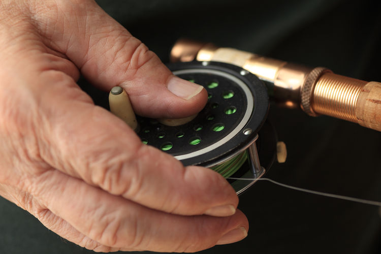 Man with hand on fishing reel Close-up Closeup Cork Fingers Fisherman Fishing Equipment Fishing Line Fly Fishing Reel Fly Fishing Rod Hand Handle Individual Sport Indoors  Metal Natural Light Textures
