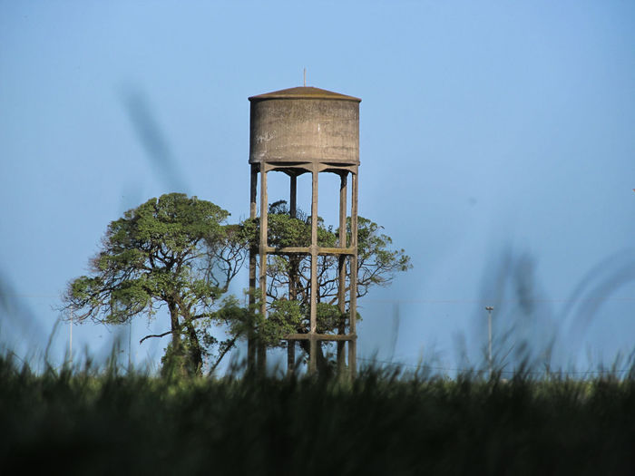 Water tower on field against sky
