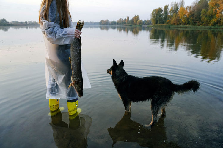 Water Domestic Animals Pets Domestic Reflection Dog Outdoors Women Nature Lifestyles Lake Real People Fish Fishing Fisherman Young Women Girl Redhead Red Hair Autimn Fall Beauty In Nature Hunting Lake View One Person Mammal Standing