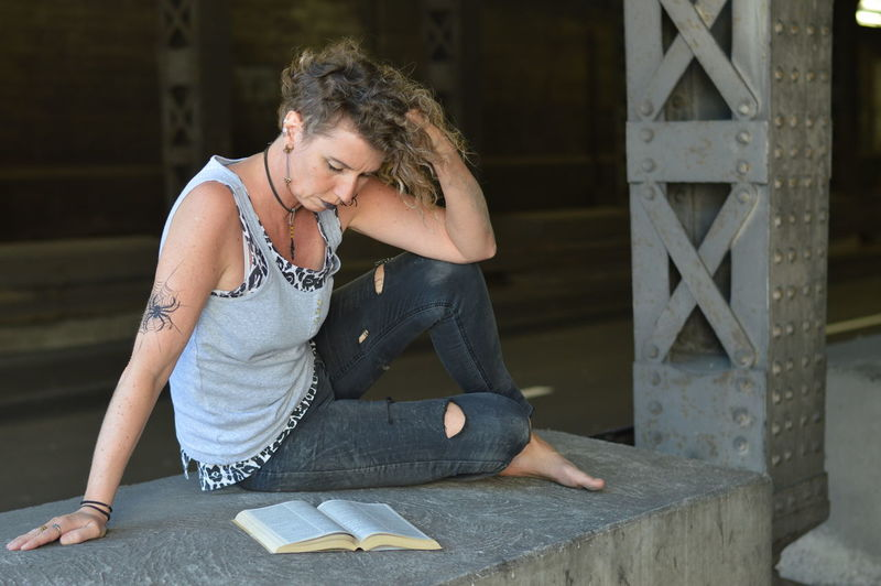 Mature woman reading book while sitting on wall