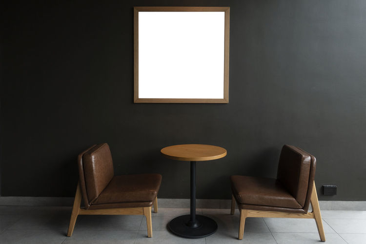 Empty chairs and table by wall at cafe