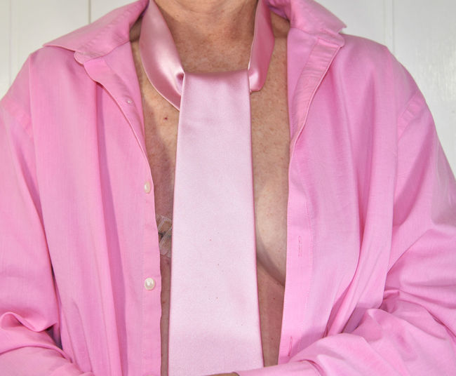 Midsection woman wearing pink shirt and tie