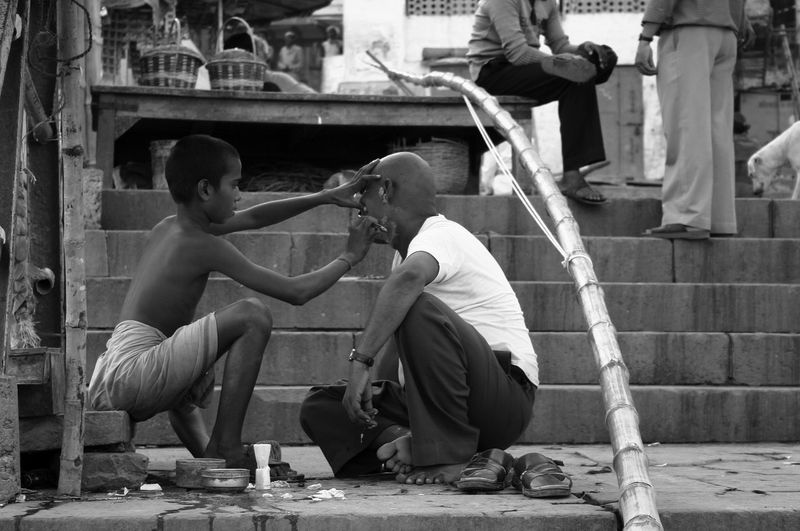 Side view of two men sitting on built structure in city