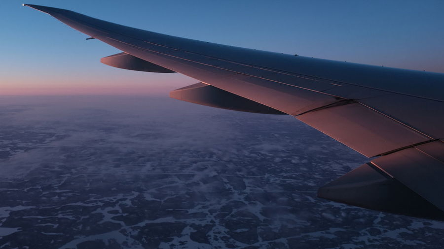 Cropped image of aircraft wing flying against sky during sunset