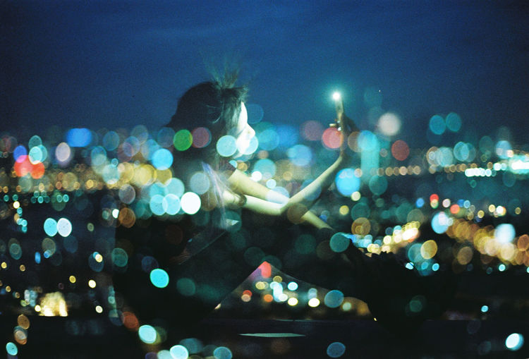 Defocused image of illuminated lights on street in city at night