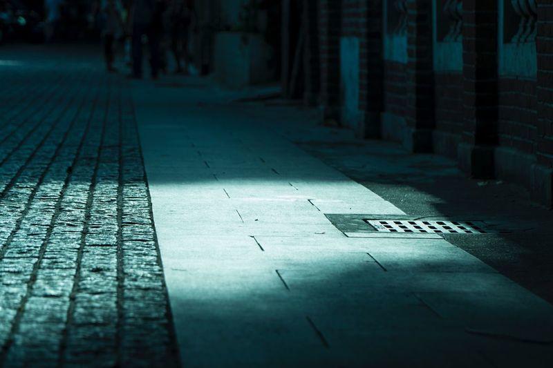 Sunlight falling on empty footpath in city