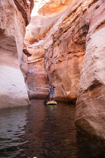 Man paddleboarding on lake amidst rock formations