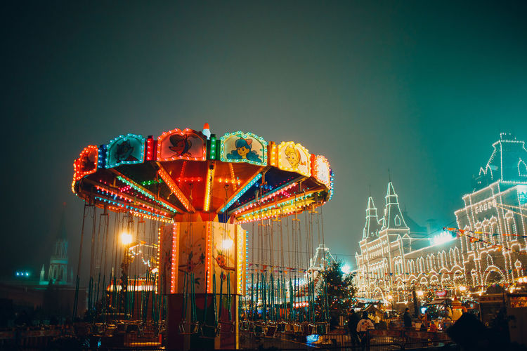 Illuminated amusement park ride against sky at night