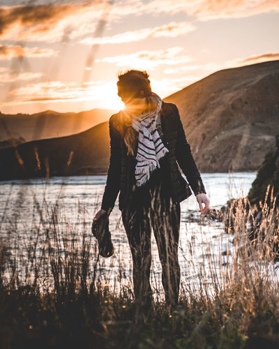 Full length of woman standing by lake against sky during sunset