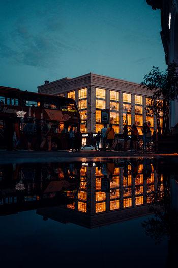 People in swimming pool against buildings in city at dusk