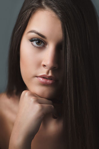 Close-up portrait of beautiful woman against gray background