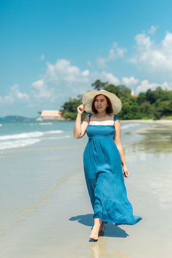 Full length of young woman standing at beach against sky