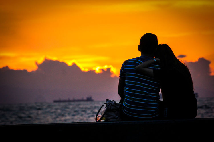 Rear view of silhouette couple against orange sunset sky