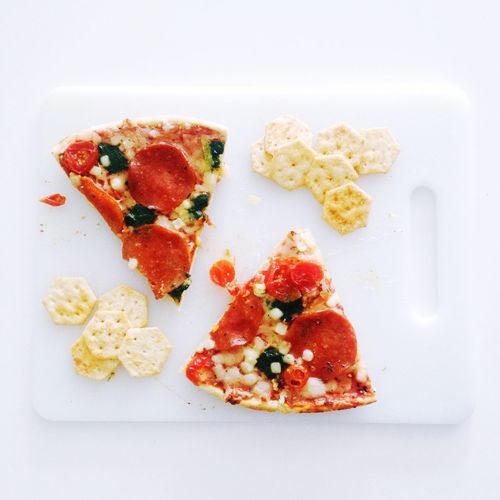 Pizza Slices And Crackers On Cutting Board