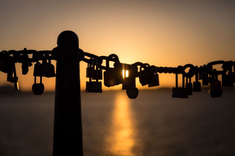 Close-up of padlocks hanging on chain against sea during sunset
