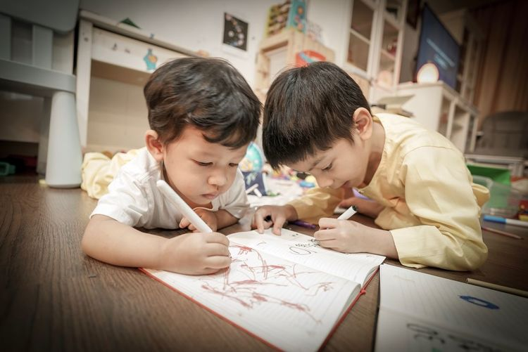 Siblings painting while lying on floor at home