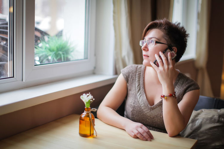 Woman answering smart phone while looking through window at home