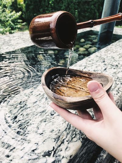 Cropped Hands Holding Bowl On Drinking Water