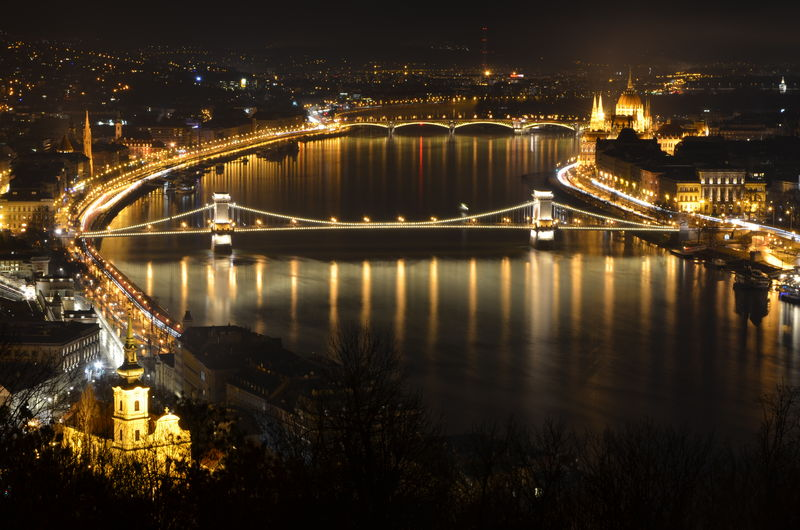 High angle view of illuminated chain bridge over river against sky at night in city