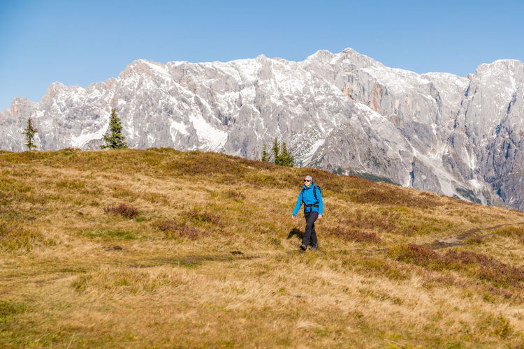 Woman hiking on footpath in alpine landscape, hochkönig, austria.