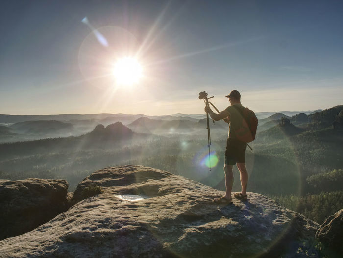 Man photographer taking photo on sunset mountain peak. hiker in shorts and backpack on sweaty bag