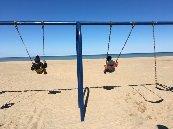 Rear view of children playing on swing at beach against clear blue sky during sunny day