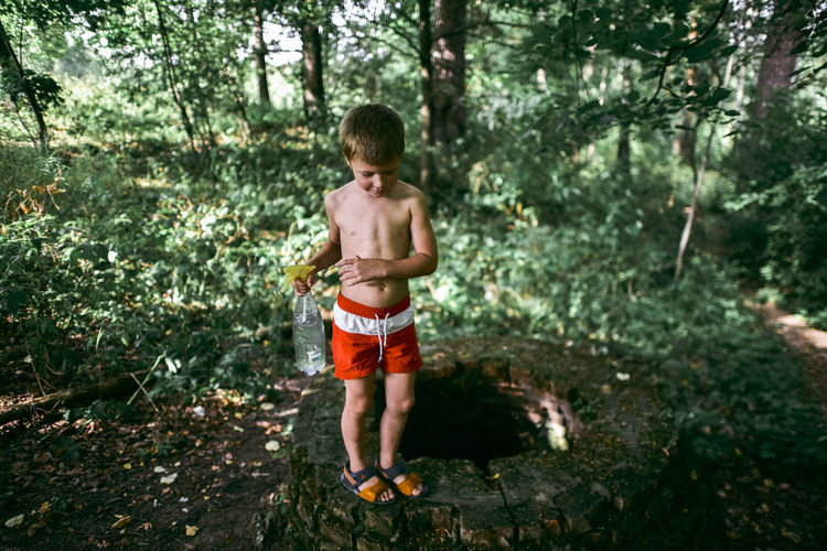 Full length of shirtless boy standing in forest