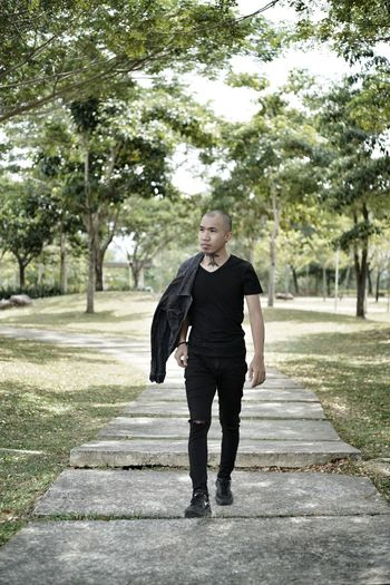 Full length portrait of man standing on footpath