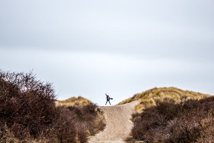 Woman Jumping On Dirt Road Amidst Bush At Hill Against Sky