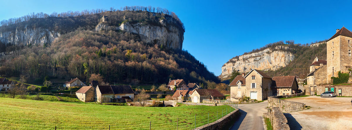 Panorama of a Baume-les-Messieurs village. Jura department of Franche-Comte. Baume-les-Messieurs is classified as one of the most beautiful villages of France Ancient Town Baume-les-messieurs Beauty In Nature Blue Sky Bourgogne-Franche-Comte Cliff Europe France French Green Lawn History Jura Department Landscape Mountain Nature Outdoors Panorama Panoramic Rock Rural Scenery Sunny Day Town Traditional Village