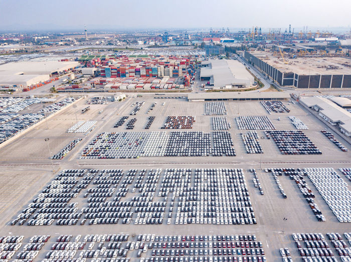 Aerial View of new cars parked at the parking area of automobile factory. Waiting for export and import at the international port. Stock Vehicle Car Port Industry Auto Export Park Industrial Transportation Transport New Row Business Trade Engineering Metal Dealership Market Parking Car Manufacturing Conveyor  Mechanical Mechanic Fuel Automotive Drive Control Top View Technology Dealer Machine Sale Factory Production Import Motor Line Up Automobile Engine Lined Storage Shipping  Aerial Delivery Company Cargo Traffic Sea Logistic